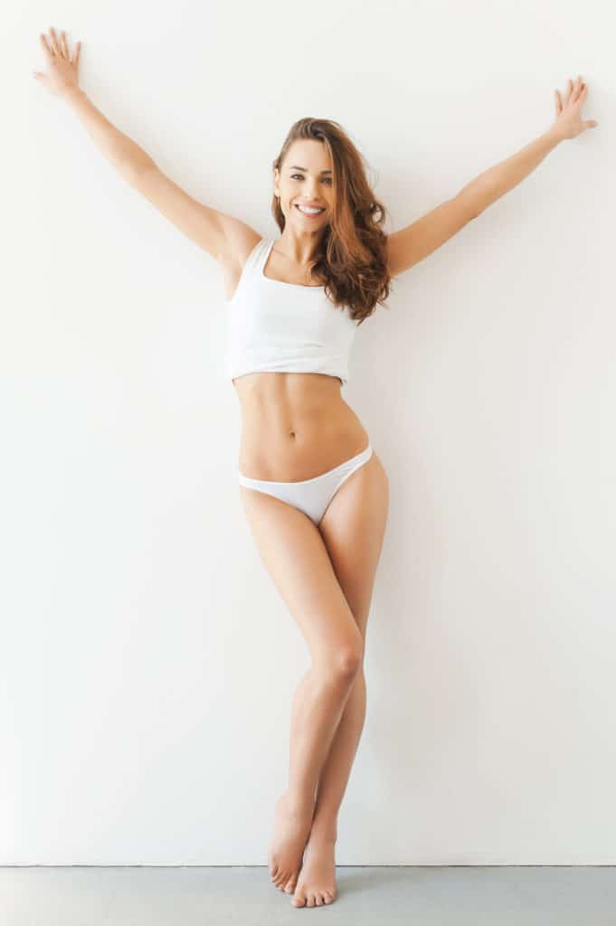 Full length of attractive young woman in white tank top and panties posing while standing against white background
